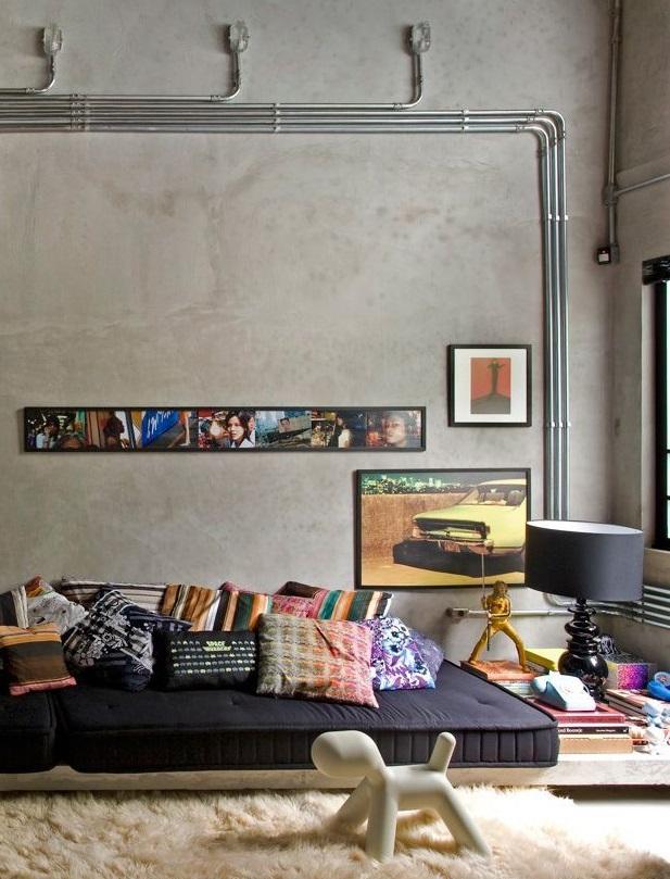 """""""Холод"""" промышленных серых стен с открытыми коммуникациями удачно нейтрализуется мягкими цветными подушками и элементами декора"""