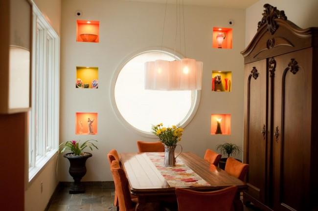 В небольшой столовой маленькие углубления в стене с украшениями и подсветкой