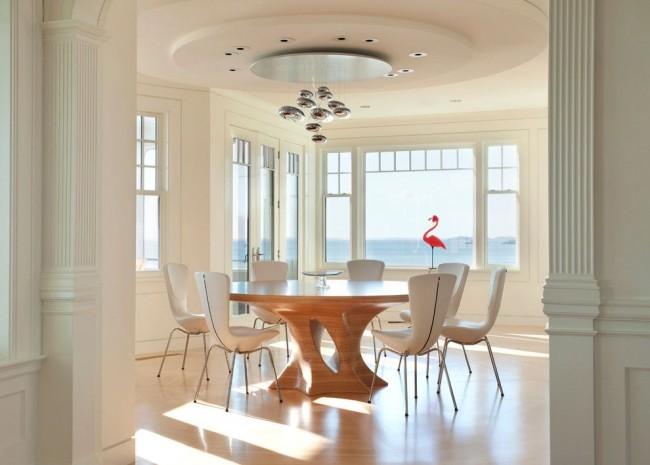 Круглый стол из светлого дерева в белой столовой выглядит дорого и красиво