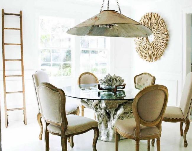 Круглый стеклянный стол закрепленный на цельном срубе окрашенном в серебряный цвет