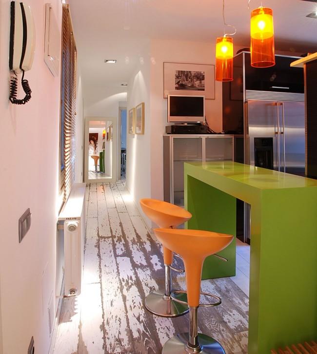 Оранжевые стулья в компании с оранжевыми светильниками и зеленым столом добавляют сочности и нескучности обычной кухне