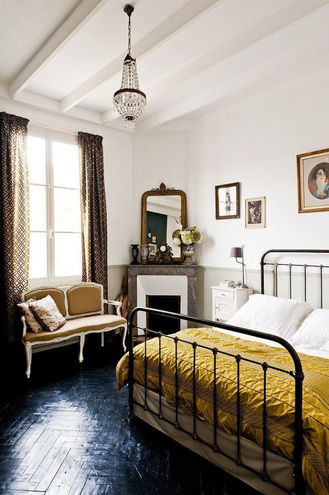 Черный паркет цвета смолы в сочетании с кованой кроватью делает комнату интересной