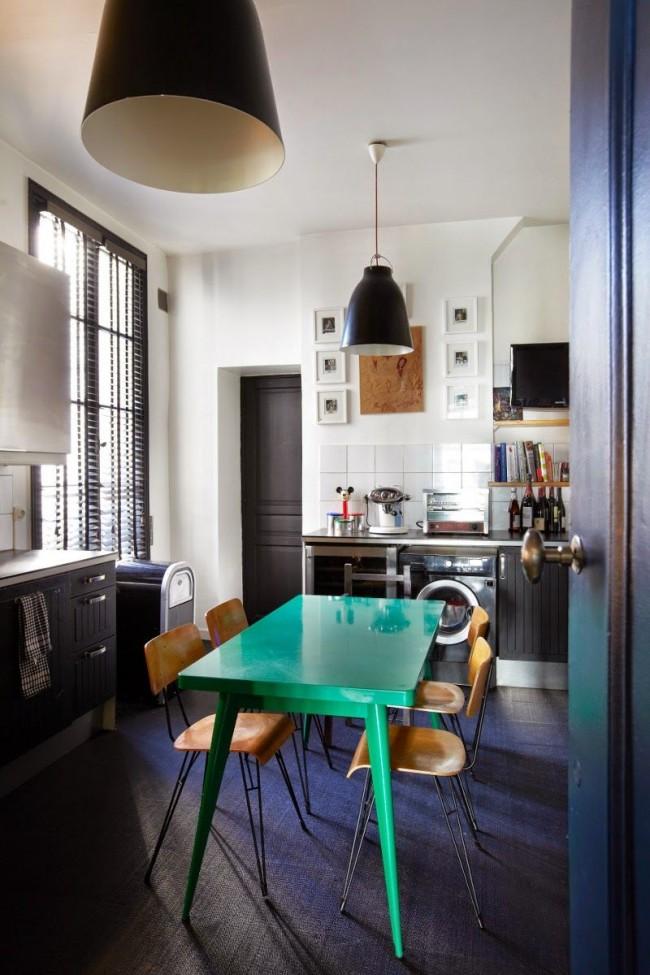 Небольшой бирюзовый стол на темном полу в центре кухни