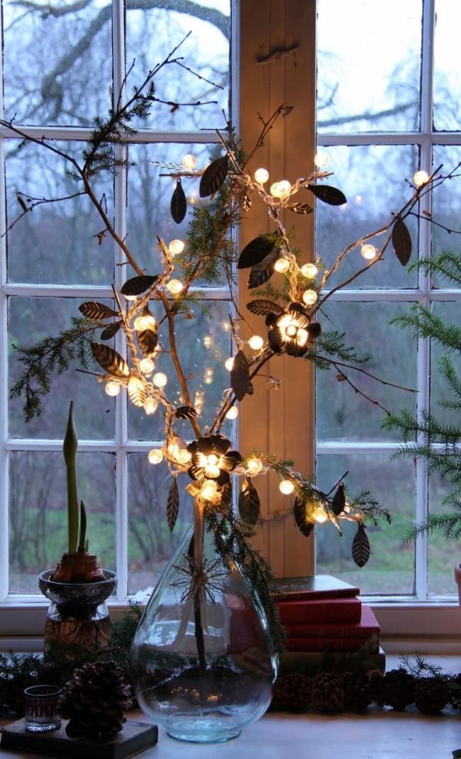 Веточка ёлки украшенная маленькой гирляндой с круглыми лампочками
