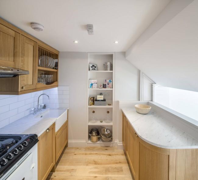 В потолках мансардных кухонь очень удобно прятать коммуникации и проводку. Обратите внимание, что высота потолка в максимальных точках должна быть не менее 2.08 м