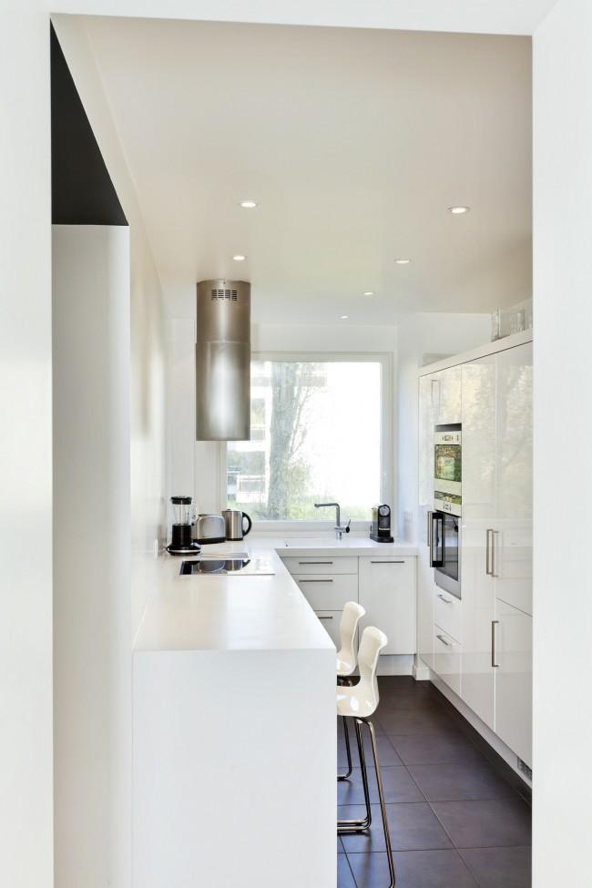 П-образная кухня в узком помещении. Варочная поверхность здесь расположена на обеденной, барной зоне