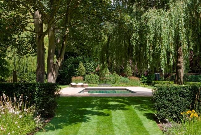 Дизайн газона можно создавать, сочетая сорта травы разных цветов, а также во время стрижек с помощью газонокосилки