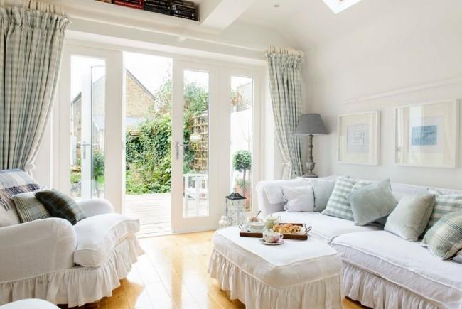 Уютный мебельный гарнитур в небольшой прованской гостиной, выполненной в белых тонах