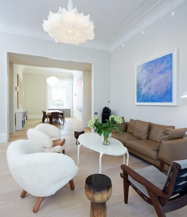Коричневый диван вносит ноту роскоши и солидности в светлый интерьер