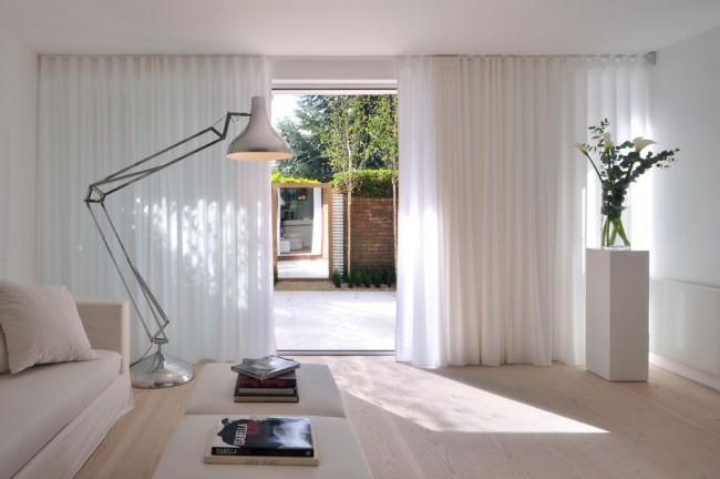 Светлый ламинат привнесет ноту тепла и уюта в бело-кремовую комнату