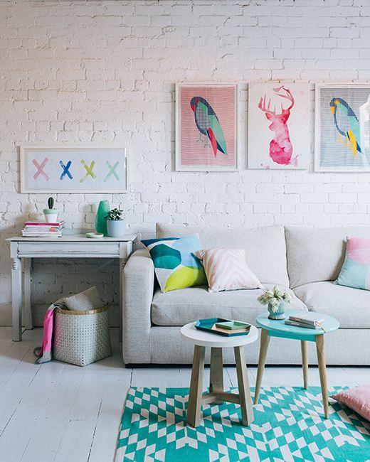 Яркие картины и коврик разбавляют сдержанный серо-белый интерьер