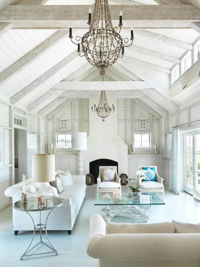 Изысканный столик со стеклянной столешницей словно парит в воздухе в интерьере белой гостиной