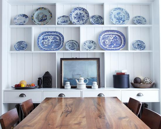 Расставленные в один ряд декоративные тарелки в гостиной