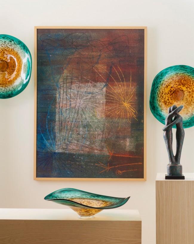 Прекрасное сочетание декоративных тарелок на стене и вазы на столике