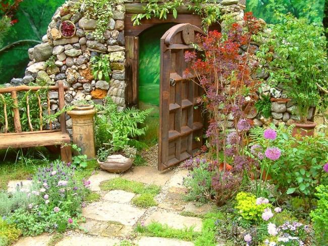 Оригинальный забор, покрашенный под зеленый луг, в деревенском стиле оформления сада