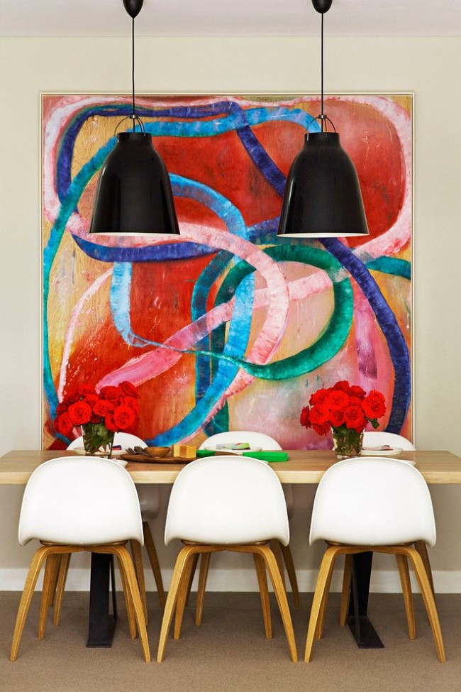 Большое яркое пятно на стене в виде картины дополняют интерьер столовой