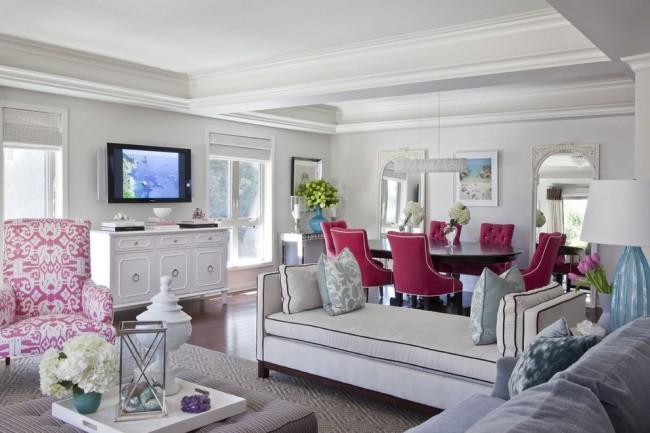 Яркая зона столовой отделена от гостиной небольшим белым диваном