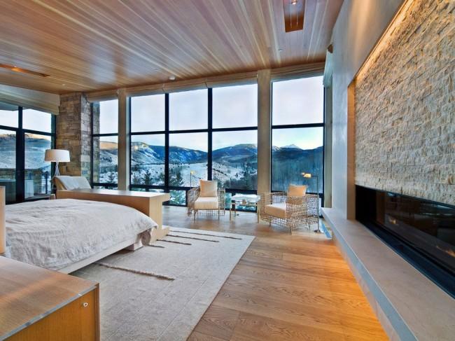 Стена из прозрачного стекла стирает границы между комнатой и участком, прилегающим к дому
