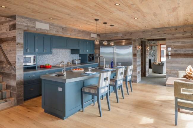 Голубая мебель и серо-бежевые тона деревянной обшивки на кухне