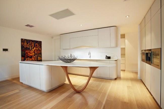 Белая кухня в стиле модерн с необычной островной частью и большой картиной