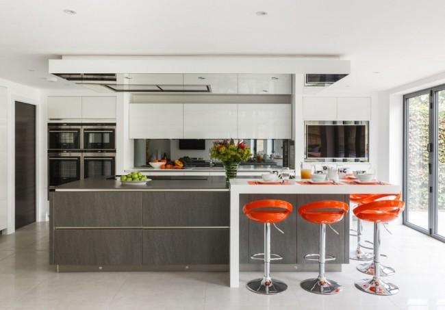 Яркие барные стулья контрастируют на фоне серо-белой кухни