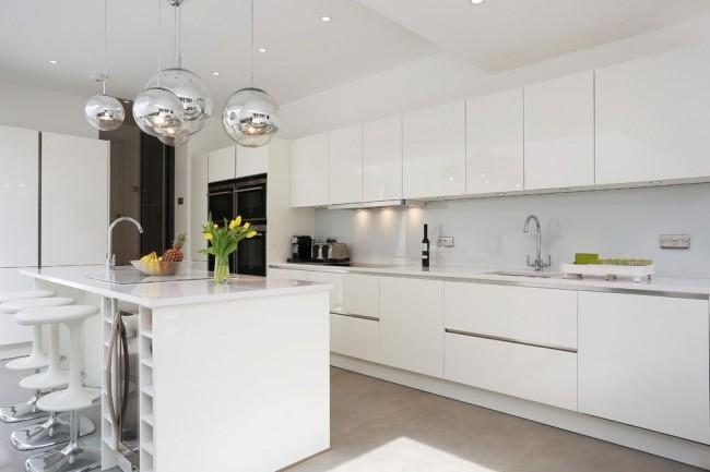 Современная стильная кухня интерьер которой дополняет аксессуар в виде шаров стального цвета, свисающих над островной частью