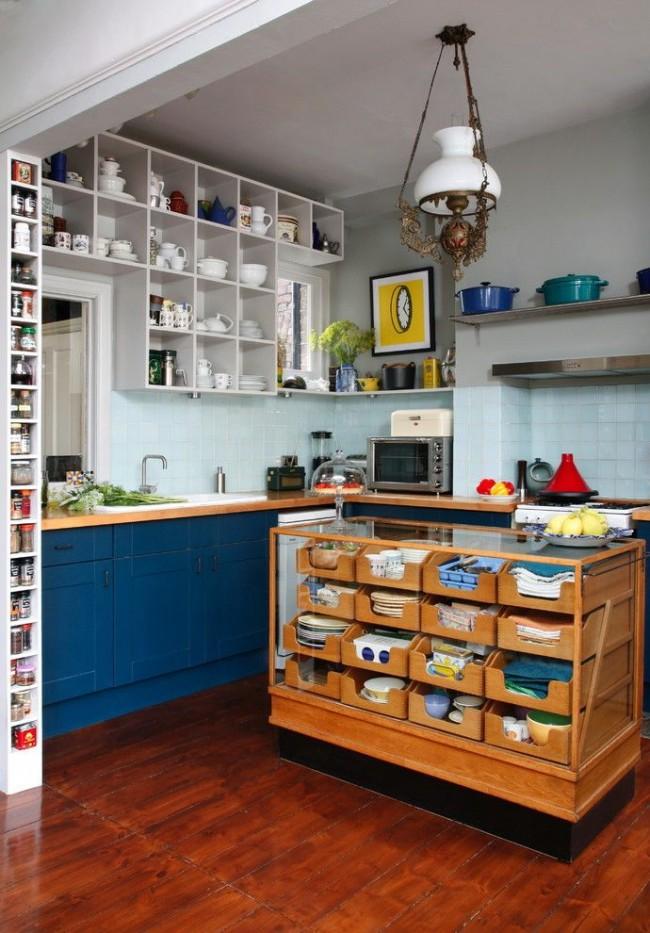 Яркая сине-белая кухня в стиле кантри с небольшим островом в центре, который является местом для хранения посуды и полотенец