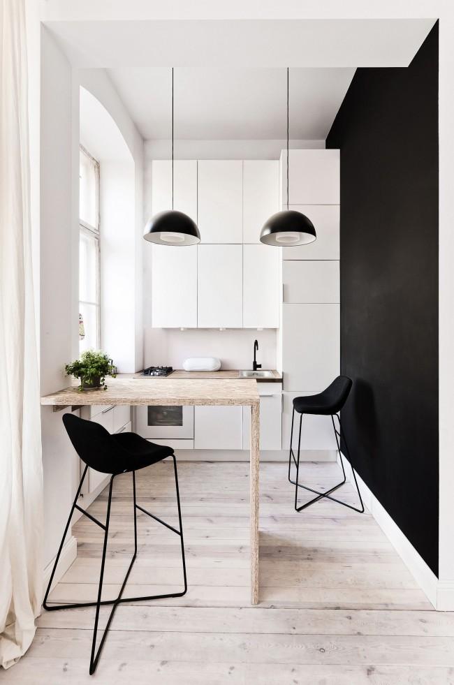 Небольшая черно-белая минималистичная кухня с обеденным столиком на двоих