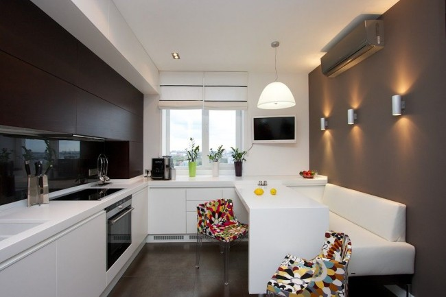 Угловой мягкий уголок в кухне экономит место, так как в этом случае не нужно выделять запас пространства для отодвигания стульев