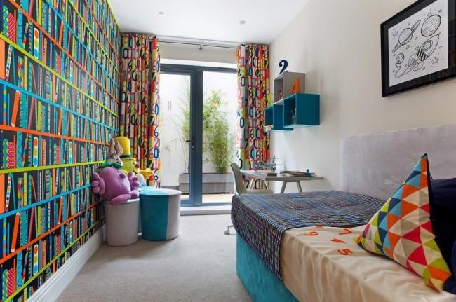 Небольшая узкая комната со всем необходимым для комфорта ребенка-школьника. Одна стена здесь полностью оклеена обоями с ярким повторяющимся рисунком