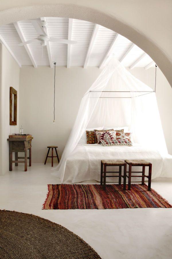Кровать под прозрачны легких балдахином в белой спальне