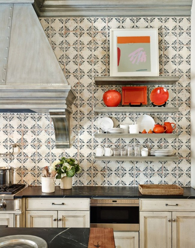 Кухня в испанских мотивах с мозаичной стенкой и ярко-оранжевыми элементами посуды и декора