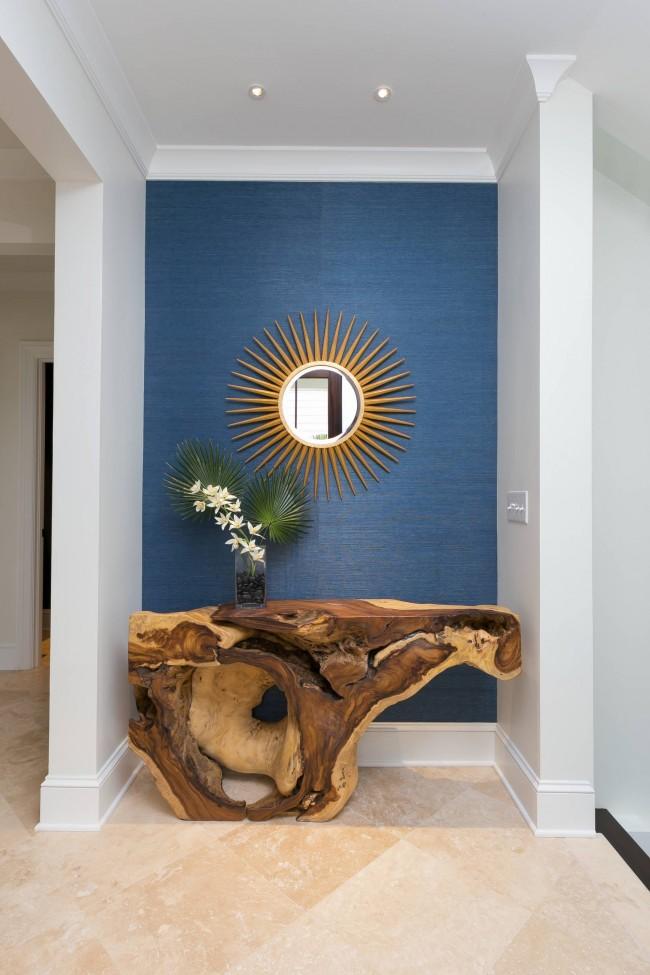 Яркое декоративное зеркало и столик из цельного куска древесины в нише