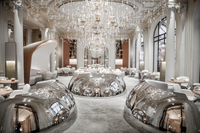"""Отполированные до зеркального блеска стальные """"клоше"""" на входе в отмеченный двумя мишленовскими звездами парижский ресторан Alain Ducasse au Plaza Athénée. Традfиции здесь встречаются с нестандартными решениями, подчеркивающими роскошь: столики не накрываются скатертями, а тыльная сторона столешниц из драгоценного дуба обита кожей"""