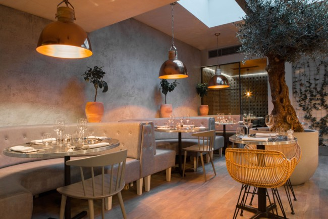 Ощущение тепла в в этом лондонском ресторане создается обильным использованием меди, а также состаренного дуба в отделке и аксессуарах. Фокус внимания во всем пространстве здесь отдан оливковому дереву, тянущемуся к солнцу под стеклянным потолком