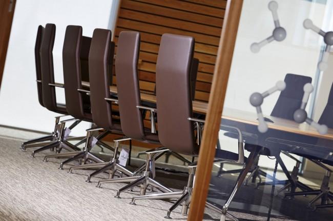 Обтянутые коричневой кожей стулья и фактурные деревянные поверхности в отделке стен одного из конференц-залов офиса и лаборатории фармацевтической компании в Кардиффе (административный округ Уэльс)