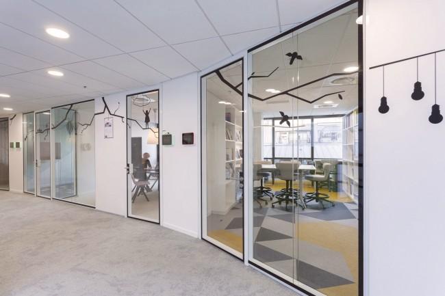 Сдержанно оформленный офис агентства недвижимости в Париже. Коридор со стеклянными дверями в кабинеты сотрудников оживляют интерьерные наклейки