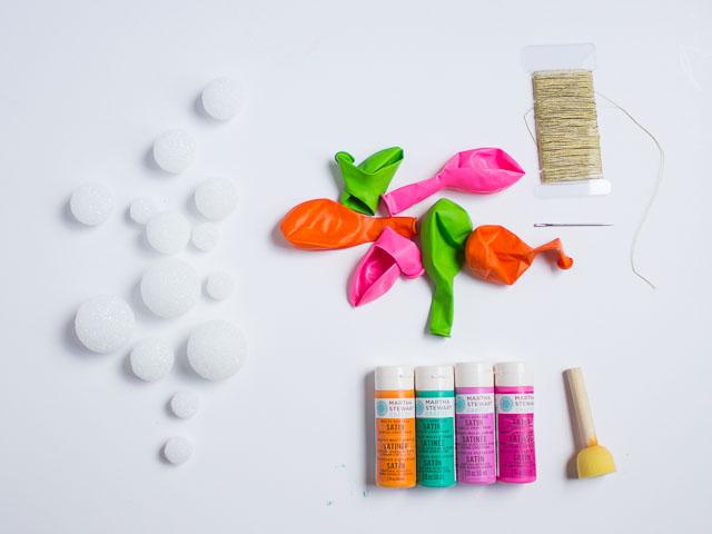 Чтобы сделать такое украшение для воздушных шаров, как на фото выше, понадобится: флористическая пена в форме шаров, краска, губка для нанесения краски, большая игла. Длина иглы должна превышать диаметр самого большого из флористических пенных шаров