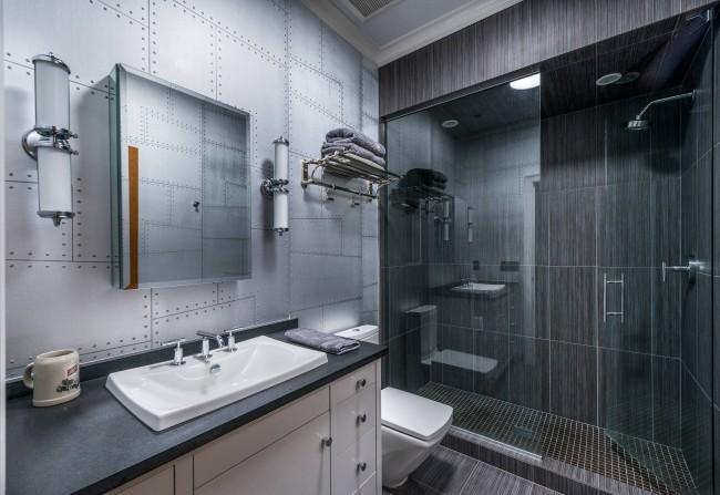 Очень мужской дизайн серой ванной комнаты, чрезмерную строгость в котором нивелирует сюжет в рисунке акцентной стены на тему клепанных листов металла