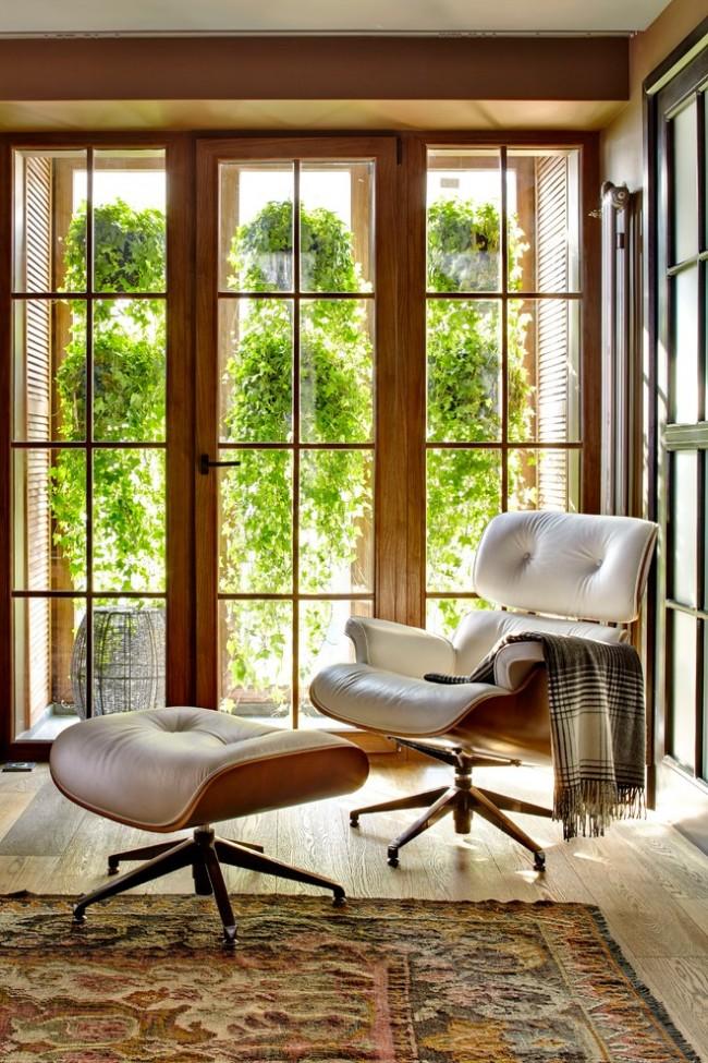Висячие сады на балконе, остекленном деревянными рамами. Такое озеленение дало возможность скрыть все, что происходит в квартире, от глаз жильцов дома напротив, без применения матированных стекол