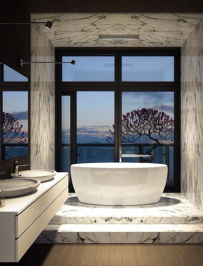 Красивое сочетание акриловой ванны и мраморной отделки помещения