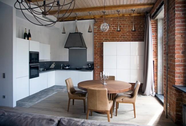 Стильная кухня в квартире-лофте. Внимание здесь привлекает сочетание глянцевых белых и теплых древесных поверхностей