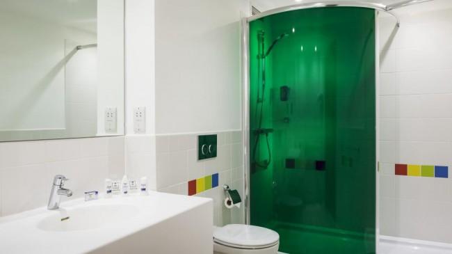 Яркая душевая кабина в углу ванной комнаты