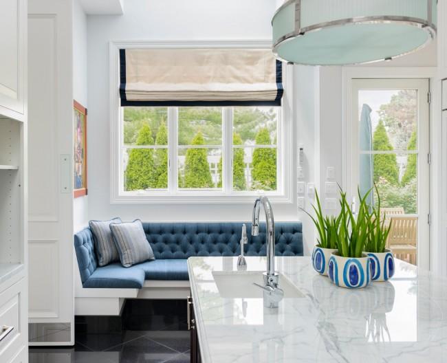 Диванчик с обивкой синего цвета под большим окном