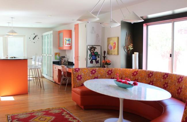 Яркий оранжевый полукруглый диван, подходящий к овальной форме стола