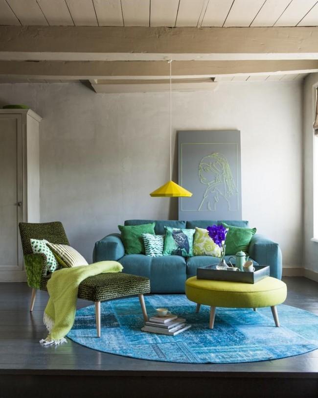 Яркий бирюзовый круглый ковер, подобранный в тон с мебелью