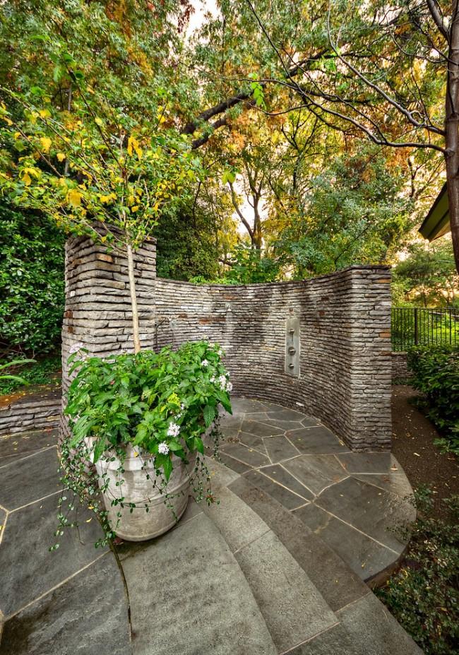 Душ, облицованный плиткой, имитирующей каменную кладку, на территории усадьбы в викторианском стиле