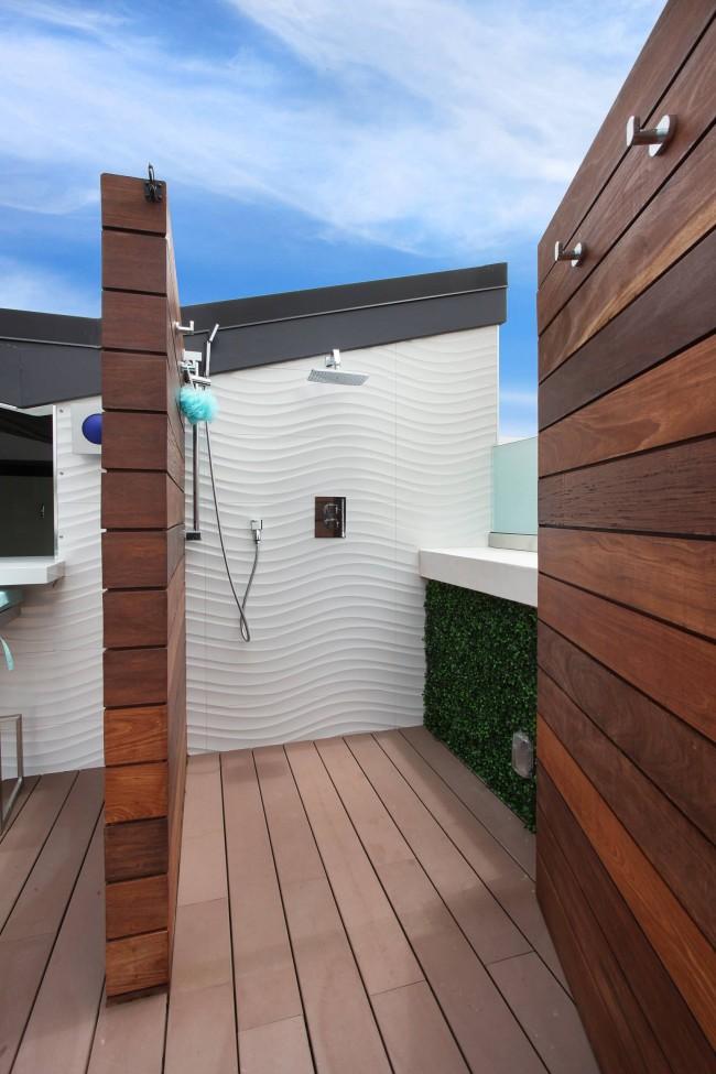 Облицованный белоснежной рельефной плиткой душ с откатным навесом, для самых требовательных эстетов. Такой вариант отлично будет смотреться возле домика на морском берегу