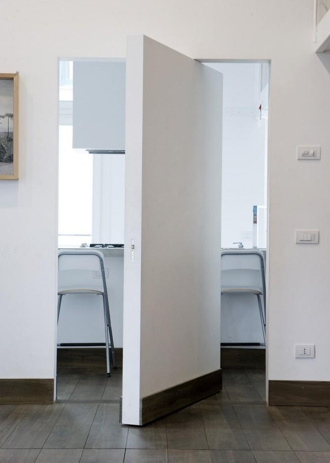 Потайная межкомнатная дверь без ручек в минималистичной тотально белой квартире