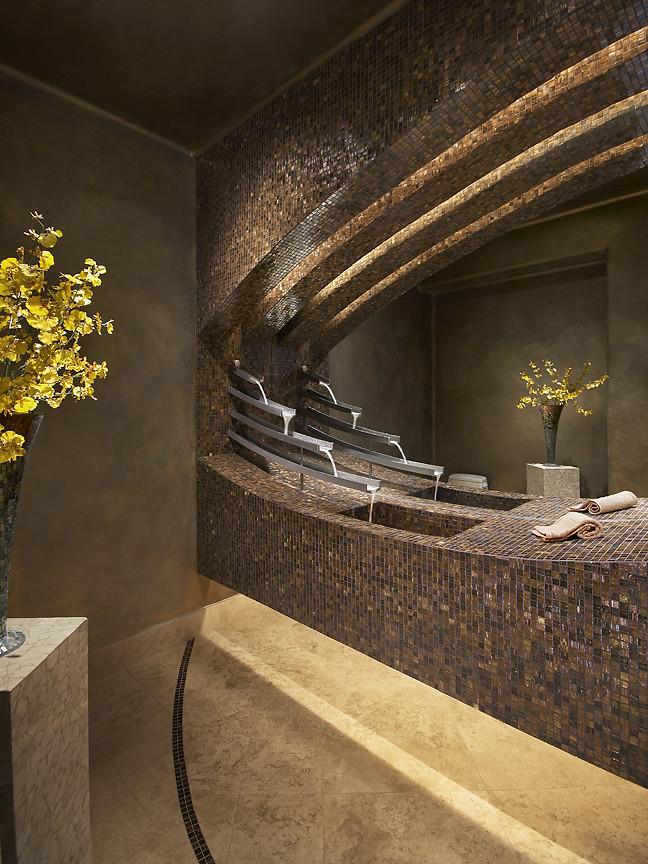 Стильный интерьер ванной комнаты с использованием мозаики: уникальный каскадный кран и скульптурные плавные линии поверхностей, облицованных мозаикой